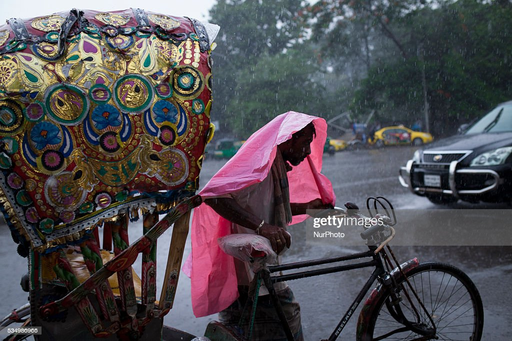 A Bangladeshi rickshaw puller makes his way through the rain in Dhaka, Bangladesh on May 28, 2016.