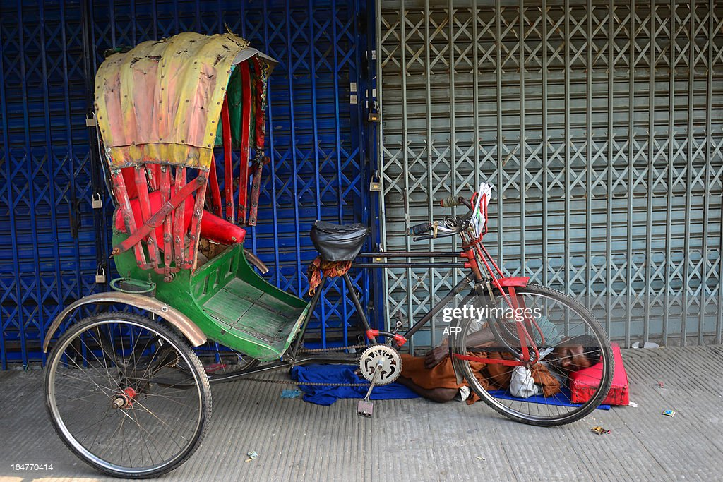 Bangladeshi rickshaw rider sleeps in front of a closed shop during a nationwide strike called by the opposition Bangladesh Nationalist Party (BNP) in protest against the detention of their leaders, in Dhaka on March 28, 2013. Schools and businesses were shut across Bangladesh on the second day of a general strike called by the country's main opposition party and Islamic allies. AFP PHOTO/Munir uz ZAMAN