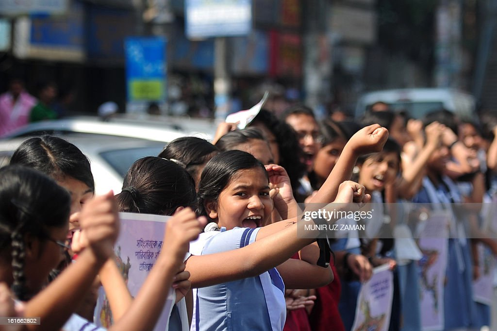 Bangladeshi school girls form a human chain as they participate in a One Billion Rising rally in Dhaka on February 14, 2013. The one-day event called for one billion women around the world to walk away from their homes, businesses, and jobs, and join together to dance in a show of collective strength. The word 'billion' refers to the one billion women who are survivors of abuse. AFP PHOTO/ Munir uz ZAMAN