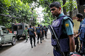 Bangladeshi security personnel stand guard near a restaurant that has reportedly been attacked by unidentified gunmen in Dhaka Bangladesh on 2 July...