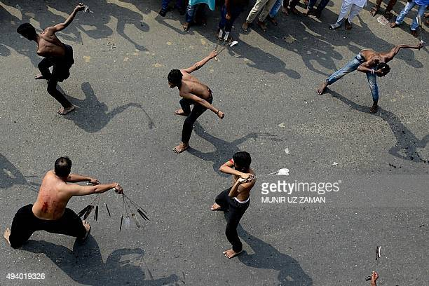 Bangladeshi Shiite Muslims wield selfflagellation chains as they take part in a religious procession of the Ashura mourning period in Dhaka on...