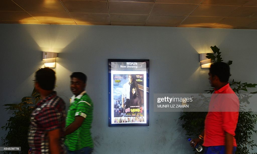 Bangladeshi shoppers walk past a film poster advertising Bangladeshi film 'Most Welcome 2' in front of a cinema hall at a shopping mall in Dhaka on September 3, 2014. Authorities in Bangladesh have banned local film-makers from giving their movies English titles after a spate of recent Bangla blockbusters with titles such as 'Honeymoon' and 'I Don't Care'. Mushfiqur Rahman Gulzar, general secretary of the Bangladesh Film Directors' Association, said the government had instructed the industry to ensure that all future homegrown releases have Bangla names. AFP PHOTO/Munir uz ZAMAN