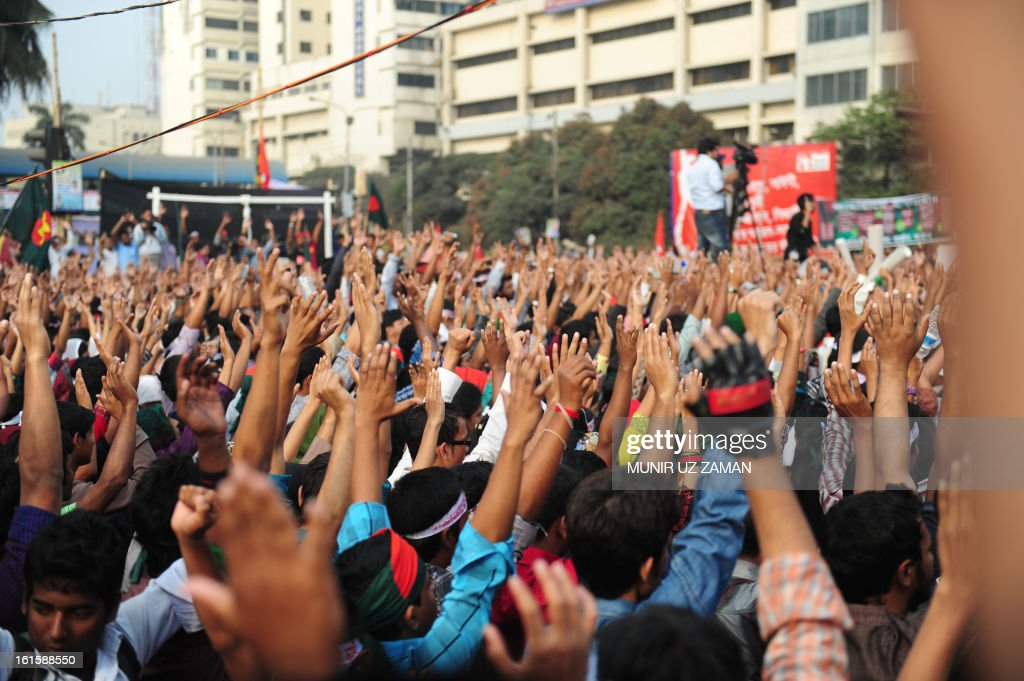 Bangladeshi social activists stand in silence and raise their hands at a key intersection in central Dhaka on February 12, 2013. Thousands of people raised hands and stood in silence or three minutes as hundreds of thousands of people stood on the streets to demand swift execution of war criminals, police and witnesses said. AFP PHOTO/ Munir uz ZAMAN