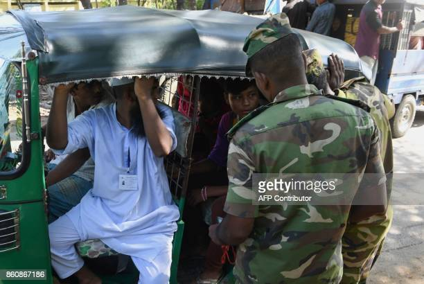 A Bangladeshi soldier questions commuters in an autorickshaw at a checkpost after Rohingya refugees were detained while attempting to sneak out of...