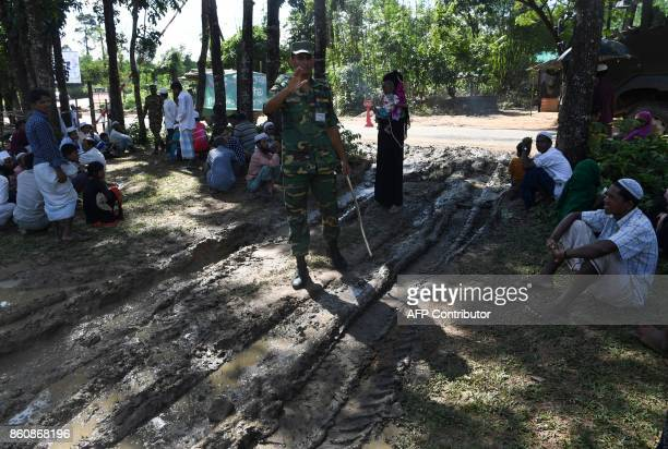 A Bangladeshi soldier speaks to Rohingya refugees who were detained while attempting to sneak out of their camps towards the city at Ukhia on October...