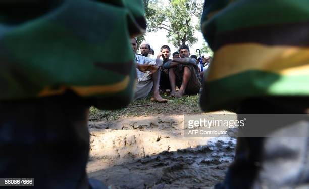 A Bangladeshi soldier stands over Rohingya refugees detained at a field while attempting to sneak out of their camps towards the city at Ukhia on...