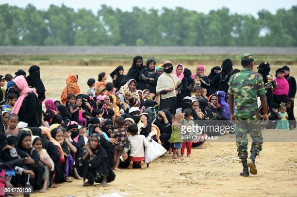 Bangladeshi soldier walks next to Rohingya refugees waiting for relief aid at Nayapara refugee camp in Teknaf on October 21 2017 Thousands of...