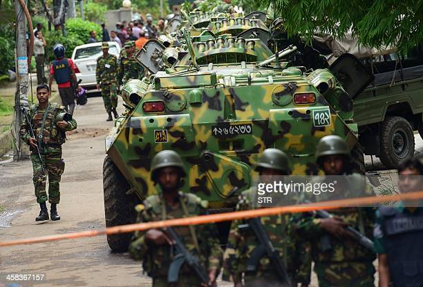Bangladeshi soldiers and police walk along a street leading to an upscale restaurant in Dhaka on July 2 following a bloody siege there by armed...