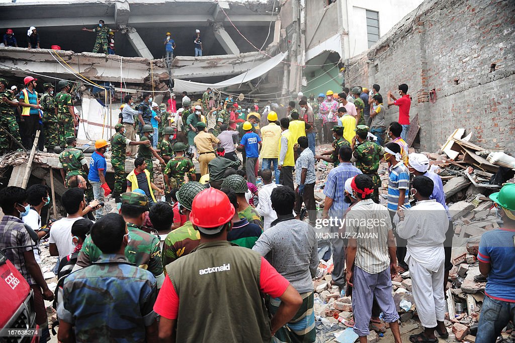 Bangladeshi soldiers assist volunteers and rescue workers looking for survivors three days after an eight-storey building collapsed in Savar, on the outskirts of Dhaka on April 27, 2013. Police arrested two textile bosses over a Bangladeshi factory disaster as the death toll climbed to 332 and distraught relatives lashed out at rescuers trying to detect signs of life. AFP PHOTO/ Munir uz ZAMAN