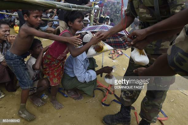 TOPSHOT Bangladeshi soldiers distribute rice to young Rohingya refugees at the refugee camp of Balukhali near Gumdhum on September 25 2017 More than...