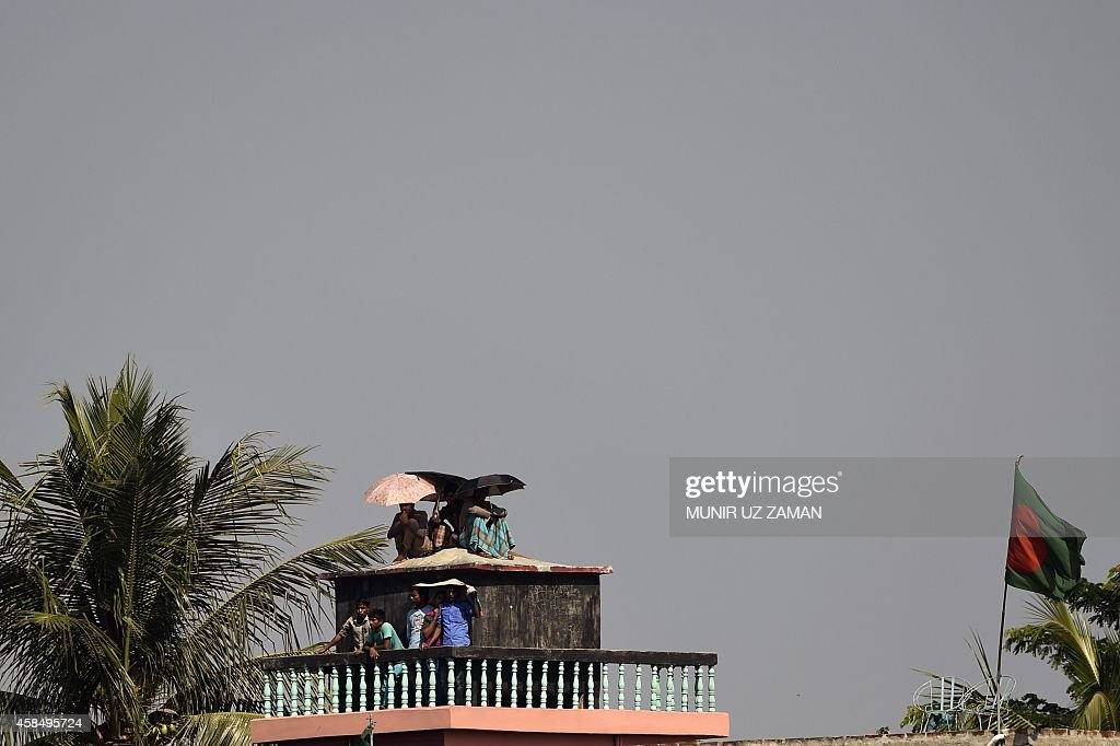 Bangladeshi spectators watch the cricket match from a roof during the fourth day of the second cricket Test match between Bangladesh and Zimbabwe at...