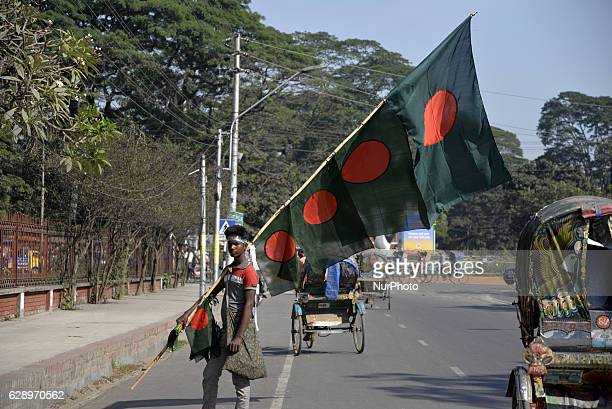 A Bangladeshi street vendor carries national flags of Bangladesh for sell to customer during the victory month of December in Dhaka Bangladesh on...