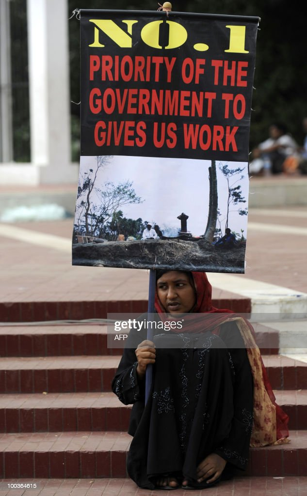 A Bangladeshi survivor of Cyclone AILA displays a placard during a mime show in Dhaka May 24, 2010. Cyclone Aila slammed into southern Bangladesh on May 26, 2009 and while the initial deathtoll was low, less than 300 people were killed , compared to 4000 by cyclone Sidr in 2007 �a huge tidal surge destroyed the network of rivers embankments. A year later the embankments have not been rebuilt, condemning 200,000 people to live in limbo�their land submerged and too salty for crops. AFP PHOTO/Munir uz ZAMAN
