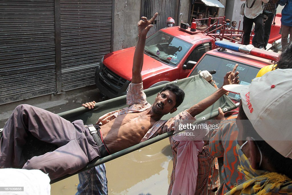 A Bangladeshi survivor reacts after he was recovered, 60 hours later, from the rubble of a collapsed eight-storey building in Savar, on the outskirts of Dhaka, on April 26, 2013. A total of 304 people are so far known to have died after the eight-storey building collapsed in the town of Savar on April 24. Rescuers are racing against time to find more survivors in searing temperatures, watched on by hundreds of anxious relatives waiting for news of their missing loved ones. AFP PHOTO/STR