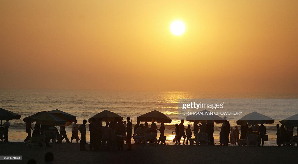 Bangladeshi tourists are silhouetted as the sun sets at a beach in Cox's Bazar Chittagong on January 7 2009 Cox's Bazar is known for its wide sandy...