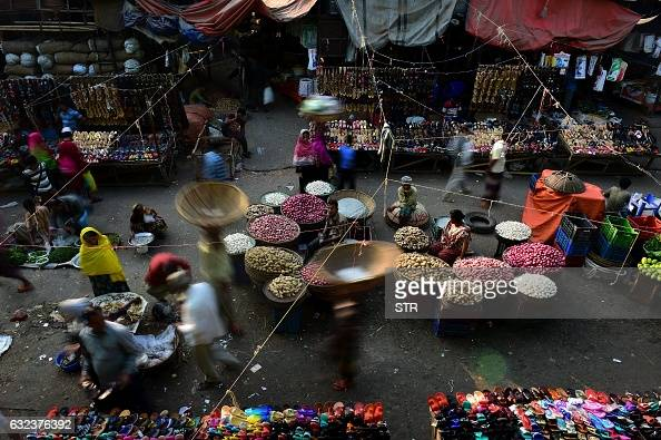 TOPSHOT Bangladeshi vegetable vendors wait for customers at a wholesale market in Dhaka on January 22 2017 Dhaka Kawran Bazar is a major business...