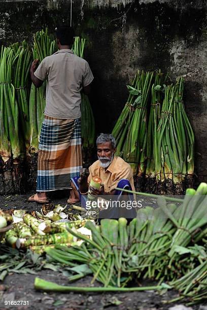 A Bangladeshi vendor preapres vegetables for sale at Karwan Bazar in Dhaka on October 7 2009 Karwan Bazar is one of the largest wholesale...
