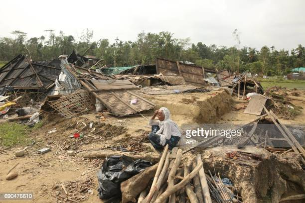 A Bangladeshi villager sits amid the desbris of a house destroyed by Cyclone Mora in Cox's Bazar on May 31 2017 Aid workers warned May 31 of an...