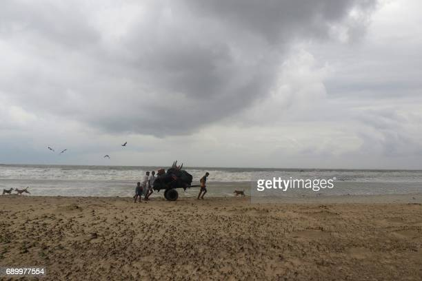 TOPSHOT Bangladeshi villagers evacuate to cyclone shelters on the coast in Cox's Bazar district on May 30 2017 Cyclone Mora hit Bangladesh on May 30...