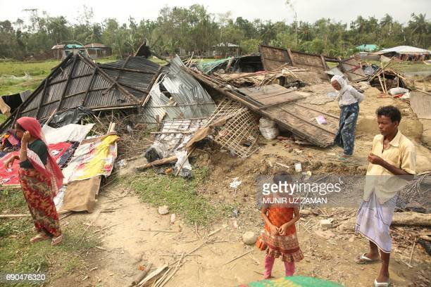 Bangladeshi villagers stand next to a house destroyed by Cyclone Mora in Cox's Bazar on May 31 2017 Aid workers warned May 31 of an 'acute crisis' in...
