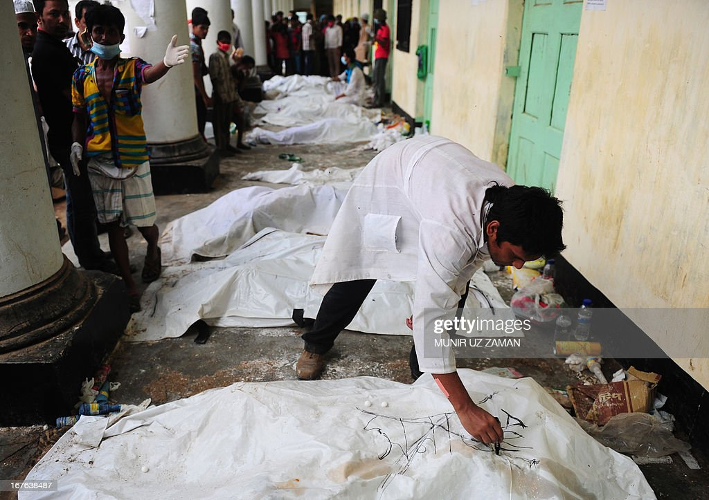 A Bangladeshi volunteer marks a dead body that was recovered from the rubble of an eight-storey building that collapsed in Savar, on the outskirts of Dhaka, on April 27, 2013. Police arrested two textile bosses over a Bangladeshi factory disaster as the death toll climbed to 332 and distraught relatives lashed out at rescuers trying to detect signs of life. AFP PHOTO/ Munir uz ZAMAN