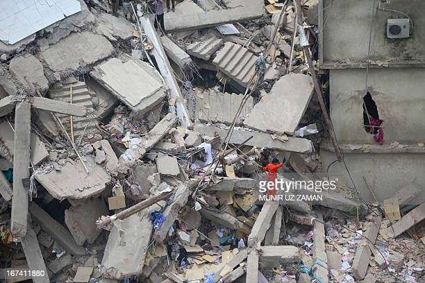 A Bangladeshi volunteer stands amid rubble as he assists in rescue operations after an eightstorey building collapsed in Savar on the outskirts of...