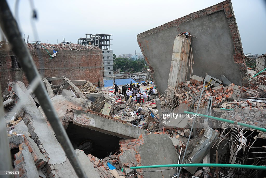 Bangladeshi volunteers and rescue workers look for survivors in an eight-storey building that collapsed in Savar, on the outskirts of Dhaka on April 28, 2013. Four people were hauled out alive overnight more than 90 hours after the disaster, but the last feeble cries for help, still audible from inside the mountain of rubble early in the day, appeared to have ended. Rescue teams at the site of a collapsed factory block in Bangladesh where 363 people have died called in heavy-lifting equipment as hopes of finding more survivors faded. AFP PHOTO/ Munir uz ZAMAN