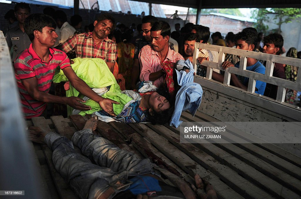 Bangladeshi volunteers and workers load dead bodies onto a truck at the site of a building collapse in Savar, on the outskirts of Dhaka, on April 24, 2013. An eight-storey building containing several garment factories collapsed in Bangladesh, killing at least 82 people and further highlighting safety problems in the clothing industry. Armed with concrete cutters and cranes, hundreds of fire service and army rescue workers struggled to find survivors in the mountain of concrete and mangled steel, which resembled the aftermath of an earthquake. AFP PHOTO/ Munir uz ZAMAN