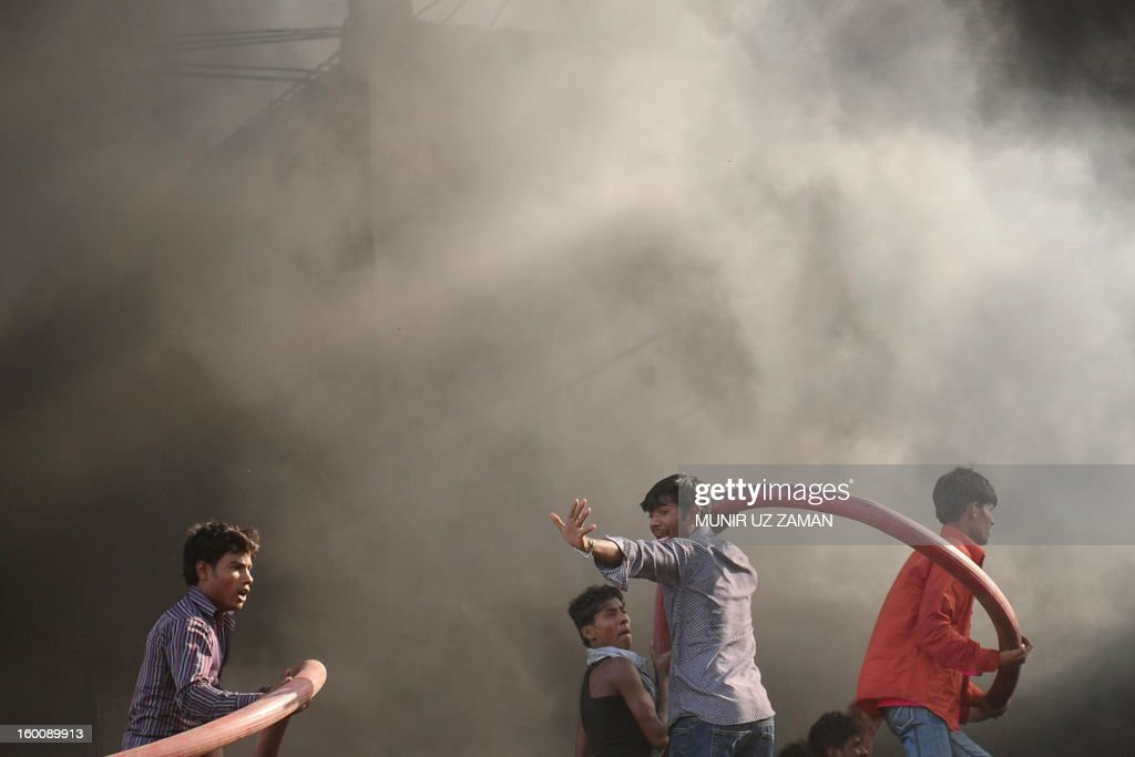 Bangladeshi volunteers assist firefighters to extinguish a blaze at a garment factory in Dhaka on January 26, 2013. At least six workers at a garment factory in the Bangladeshi capital were killed in a stampede as a fire broke out. AFP PHOTO/Munir uz ZAMAN