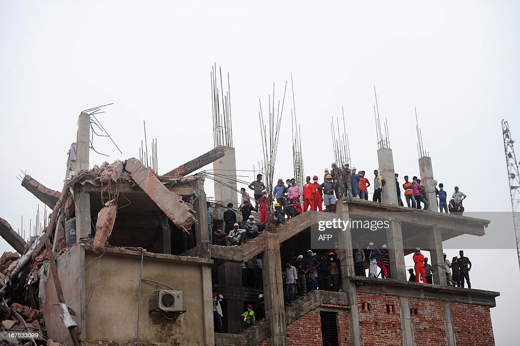 Bangladeshi volunteers watch ongoing rescue operations after an eight-storey building collapsed in Savar, on the outskirts of Dhaka, on April 26, 2013. A total of 304 people are so far known to have died after the eight-storey building collapsed in the town of Savar on April 24. Rescuers are racing against time to find more survivors in searing temperatures, watched on by hundreds of anxious relatives waiting for news of their missing loved ones. AFP PHOTO/ MUNIR UZ ZAMAN