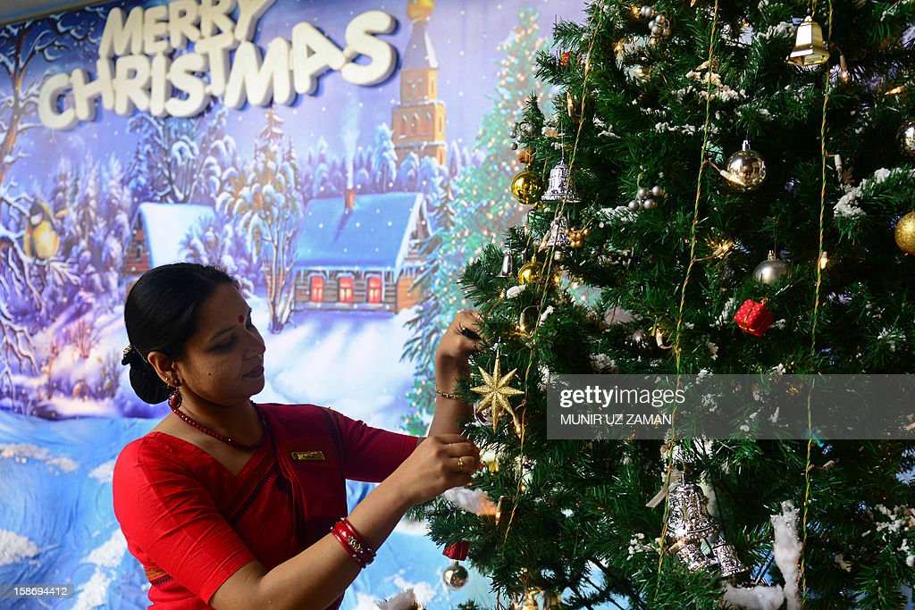 A Bangladeshi woman decorates a tree in Dhaka on Christmas Eve, December 24, 2012. Bangladeshi Christians make up only 0.08 percent of the population of the predominatly Muslim nation. AFP PHOTO/ Munir uz ZAMAN