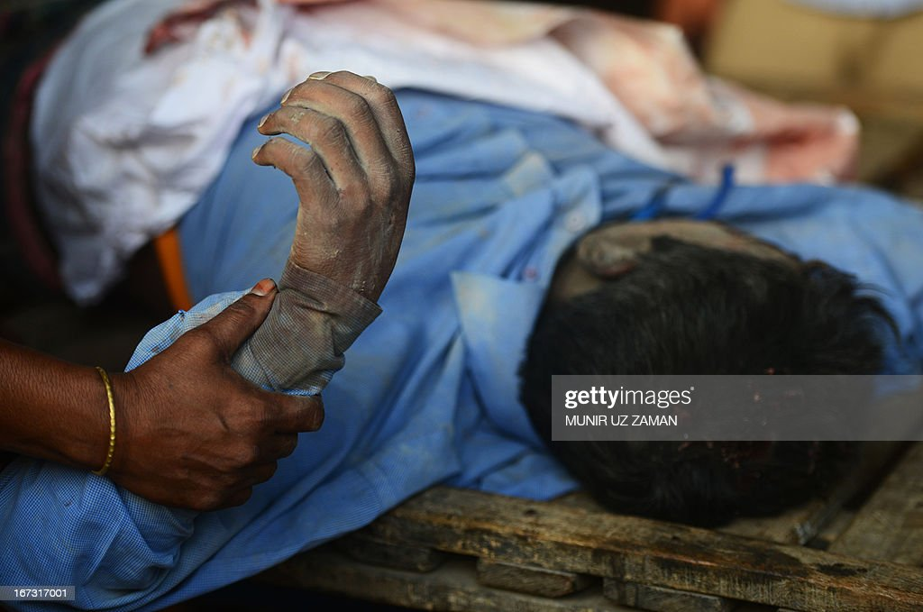 A Bangladeshi woman holds her dead husbands hand after a building collapse in Savar, on the outskirts of Dhaka, on April 24, 2013. An eight-storey building containing several garment factories collapsed in Bangladesh, killing at least 82 people and further highlighting safety problems in the clothing industry. Armed with concrete cutters and cranes, hundreds of fire service and army rescue workers struggled to find survivors in the mountain of concrete and mangled steel, which resembled the aftermath of an earthquake. AFP PHOTO/ Munir uz ZAMAN