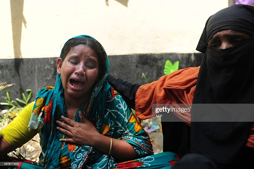 A Bangladeshi woman is comforted as she cries for her missing son, believed to be trapped in the rubble of an eight-storey building collapse in Savar, on the outskirts of Dhaka,on May 2, 2013. Bangladesh authorities have suspended the mayor of Savar satellite town outside the capital for approving the faulty construction of a building that collapsed last week, killing 429 people. AFP PHOTO/ Munir uz ZAMAN