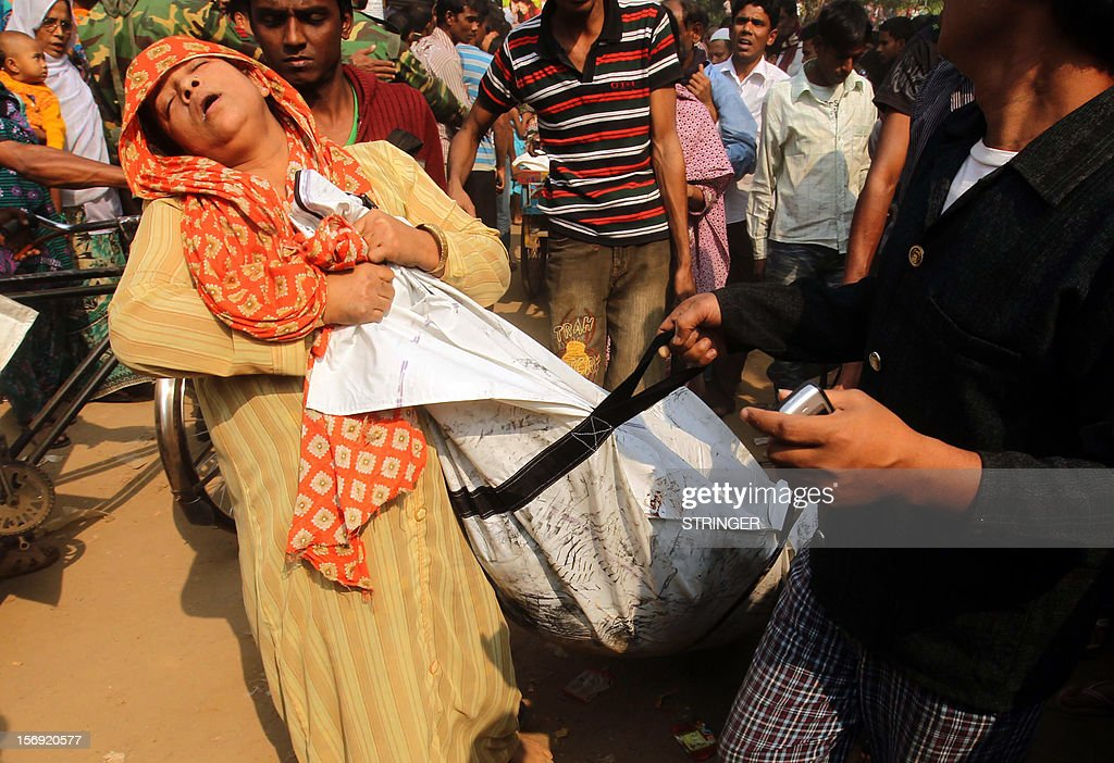 A Bangladeshi woman mourns as she holds the body of a relative who died in a fire in the nine-storey Tazreen Fashion plant in Savar, about 30 kilometres north of Dhaka on November 25, 2012. Rescue workers in Bangladesh recovered 109 bodies on Sunday after a fire tore through a garment factory, forcing many workers to jump from high windows to escape the smoke and flames. AFP PHOTO