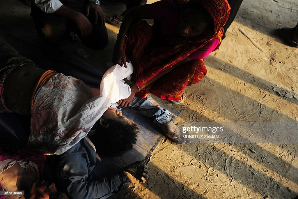 A Bangladeshi woman reacts after seeing her relatives dead body at the site of a building collapse in Savar, on the outskirts of Dhaka, on April 24, 2013. An eight-storey building containing several garment factories collapsed in Bangladesh, killing at least 82 people and further highlighting safety problems in the clothing industry. Armed with concrete cutters and cranes, hundreds of fire service and army rescue workers struggled to find survivors in the mountain of concrete and mangled steel, which resembled the aftermath of an earthquake. AFP PHOTO/ Munir uz ZAMAN