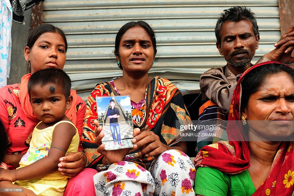 A Bangladeshi woman shows a portrait of her missing brother, believed trapped in the rubble following the collapse of an an eight-storey building in Savar, on the outskirts of Dhaka, on April 25, 2013. Survivors cried out to rescuers April 25 from the rubble of a block of garment factories in Bangladesh that collapsed killing 175 people, sparking criticism of their Western clients. AFP PHOTO/Munir uz ZAMAN