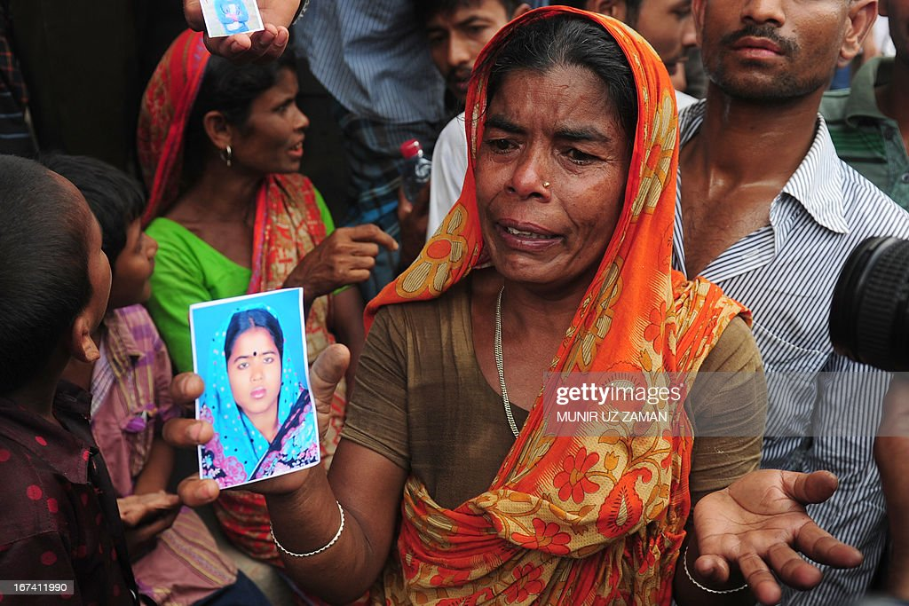 A Bangladeshi woman shows a portrait of her missing daughter in-law, believed trapped in the rubble following the collapse of an an eight-storey building in Savar, on the outskirts of Dhaka, on April 25, 2013. Survivors cried out to rescuers April 25 from the rubble of a block of garment factories in Bangladesh that collapsed killing 175 people, sparking criticism of their Western clients. AFP PHOTO/Munir uz ZAMAN