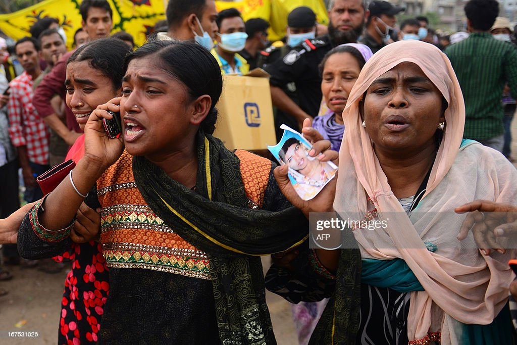 A Bangladeshi woman uses her cell phone as she holds a portrait of her missing sister, believed trapped in the rubble 60 hours after an eight-storey building collapsed in Savar, on the outskirts of Dhaka, on April 26, 2013. A total of 304 people are so far known to have died after the eight-storey building collapsed in the town of Savar on Wednesday morning. Rescuers are racing against time to find more survivors in searing temperatures, watched on by hundreds of anxious relatives waiting for news of their missing loved ones.
