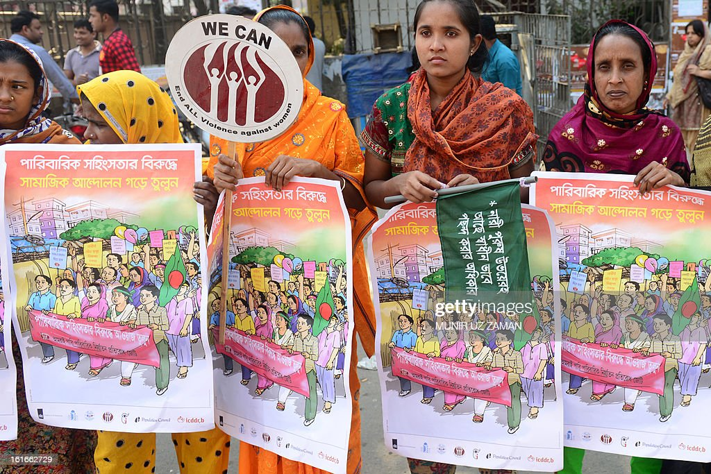Bangladeshi women form a human chain as they participate in a One Billion Rising rally in Dhaka on February 14, 2013. The one-day event called for one billion women around the world to walk away from their homes, businesses, and jobs, and join together to dance in a show of collective strength. The word 'billion' refers to the one billion women who are survivors of abuse. AFP PHOTO/ Munir uz ZAMAN