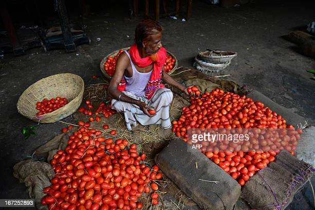 A Bangladeshi worker sorts tomatoes at a wholesale market in Dhaka on April 23 during a nationwide strike called by the Bangladeshi Nationalist Party...