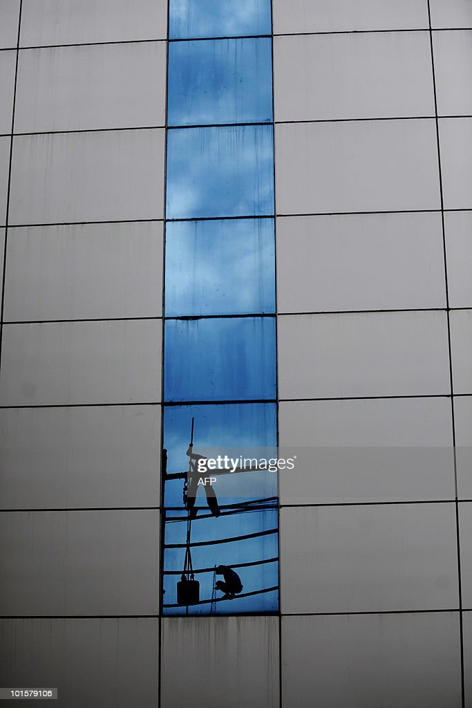 Bangladeshi workers at a building site are reflected in the glass of an adjacent building in Dhaka on April 27, 2010. Bangladesh is one of the poorest nations on the planet with 40 percent of its 144 million people living on less than 1 dollar a day. AFP PHOTO/Munir uz ZAMAN