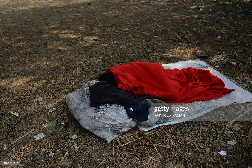 A Bangladeshi wraps himself in a blanket as he rests in a park in Dhaka on January 10, 2013. Around 80 people have died in the past week due to cold related diseases such as pneumonia as mercury dropped to the lowest in tropical Bangladesh's history, officials said Thursday. Weather and Red Crescent Society officials said the toll was expected to grow as the cold wave that's been sweeping the country for the last week was set to linger two more days, affecting a quarter of the country's 153 million people. AFP PHOTO/Munir uz ZAMAN
