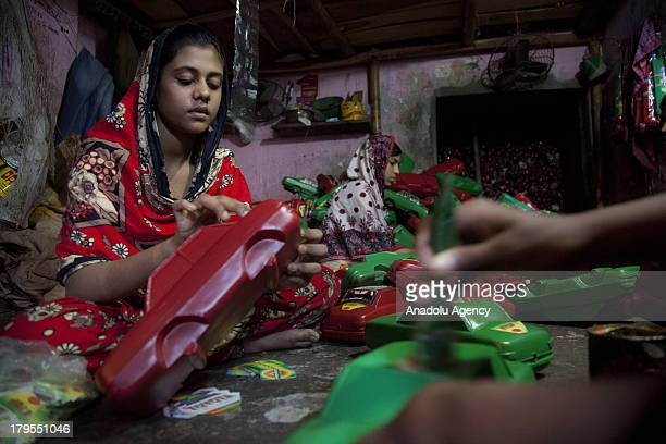 Bangladeshi young women make toy cars from recycled plastic on May 27 2013 in Dhaka Bangladesh Recycling workers in Bangladesh one of the world's...