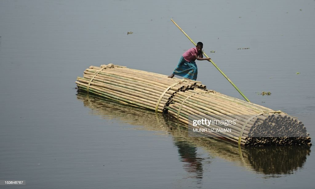 A Bangladeshi youth rafts piles of bamboos along a waterway in Dhaka on April 5, 2012. The bamboo industry has now started to export to European and Asian markets producing non -traditional food items from areas in the Chittagong Hills. Some 45 percent of Bangladesh's population are employed in the agriculture industry - many in the production of cereals including wheat and maize. AFP PHOTO/Munir uz ZAMAN
