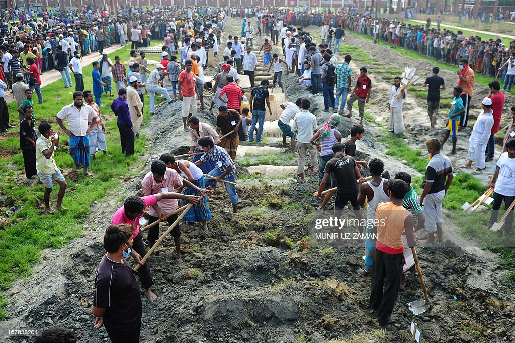 Bangladeshis bury the remains of garment workers killed in the garment factory collapse at a graveyard in Dhaka on May 1, 2013. Tens of thousands of Bangladeshis joined May Day protests Wednesday to demand the execution of textile bosses over the collapse of a factory complex, as rescuers warned the final toll could be more than 500. AFP PHOTO/Munir uz ZAMAN