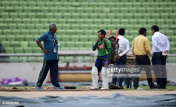 Bangladesh's cricket captain Mushfiqur Rahim reacts after looking at the pitch as he walks among groundstaff towards an indoor training session at...