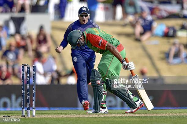 Bangladesh's Mahmud Ullah limps from the field after being bowled and hit on the foot by the ball as Scotland's Matt Machan reacts during the Pool A...