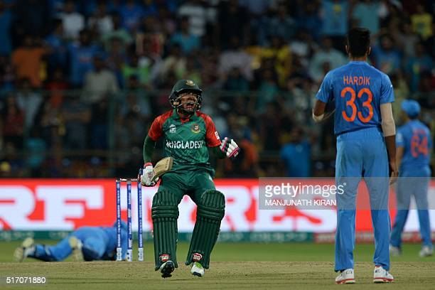 Bangladesh's Mushfiqur Rahim reacts after scoring a boundary as Indian bowler Hardik Pandaylooks on during the World T20 cricket tournament match...