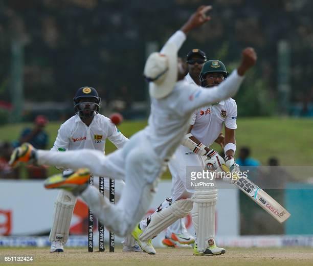 Bangladesh's Soumya Sarkar and Sri Lanka's wicketkeeper Niroshan Dickwella watch as Sri Lanka's Dinesh Chandimal drops a catch during the fourth day...