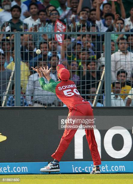 Bangladesh's Soumya Sarkar leans across the boundary line to take a catch to dismiss Pakistan's Mohammad Hafeez during the World T20 cricket...
